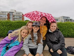 girls smiling at camera in the rain