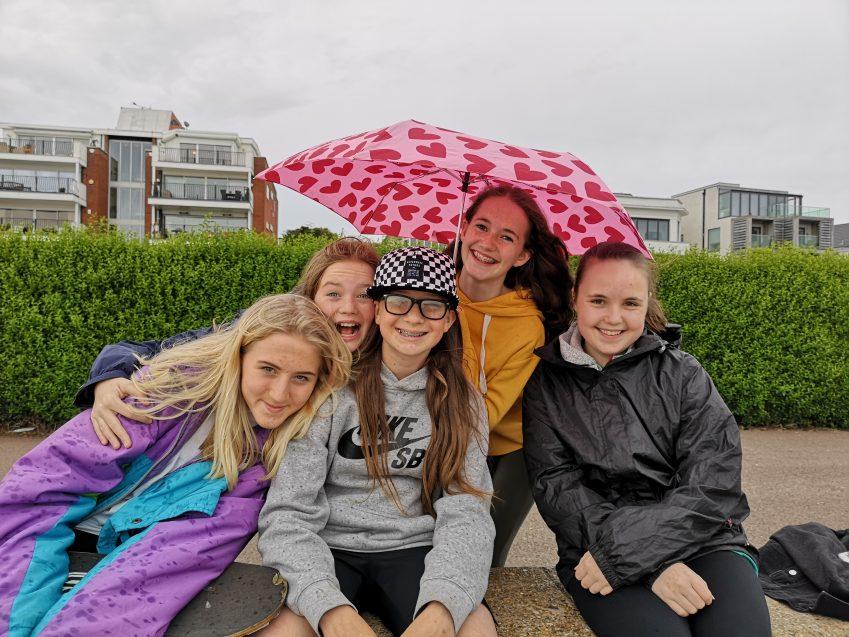 girls smiling at camera in the rain