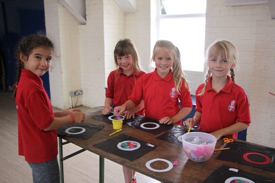 n:vestigate girls doing craft around table