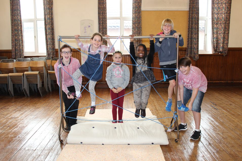 children and young people playing and climbing on frame