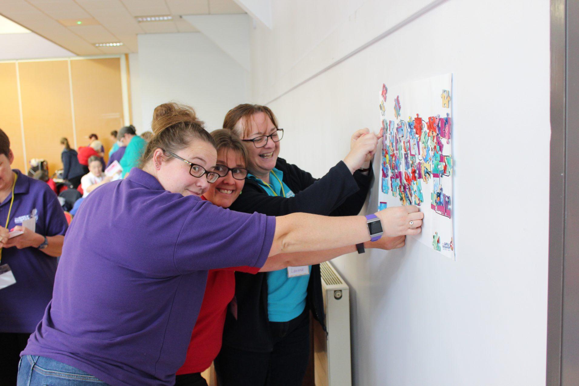 Girls' Brigade volunteers sticking jigsaw pieces to display