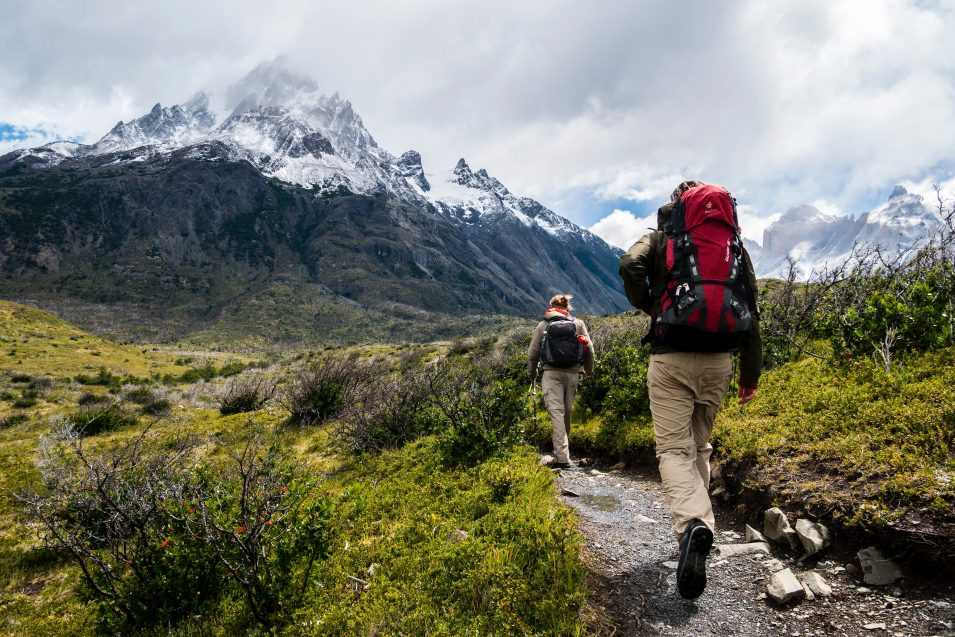 man and woman hiking towards mountain with backpacks