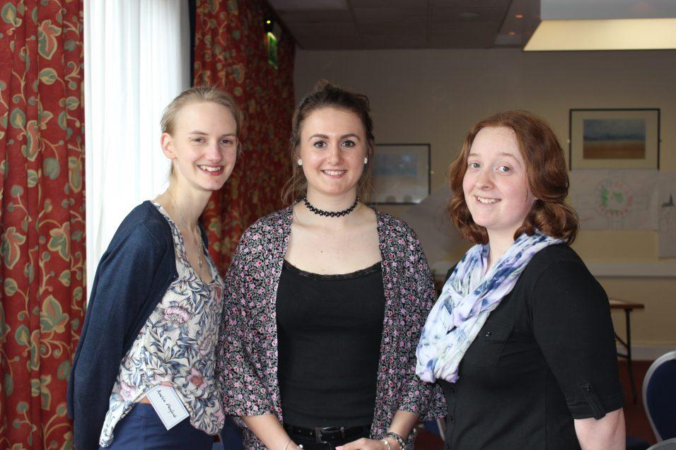 three young women smiling at camera