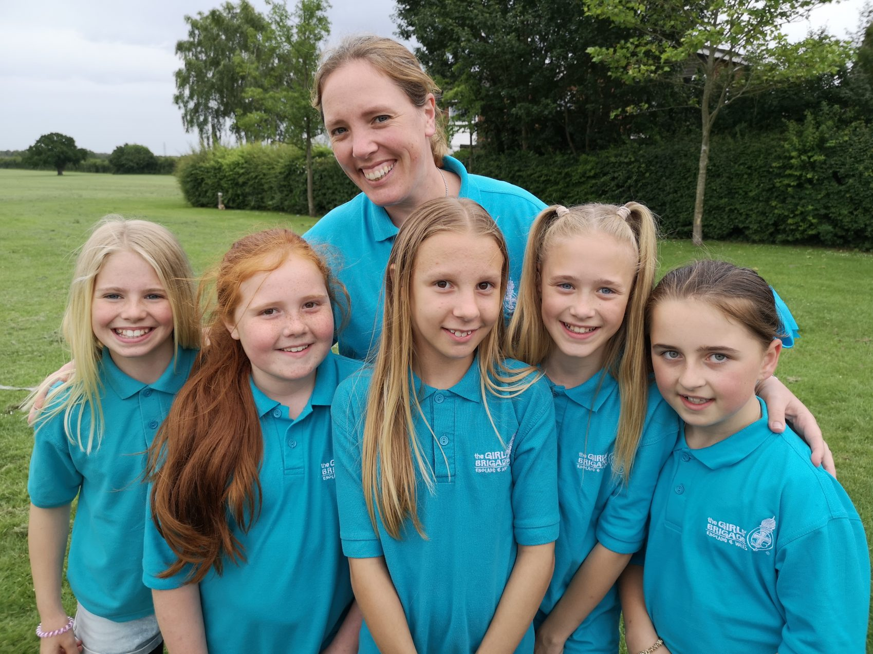 Girls' Brigade volunteer with arms around n:gage girls