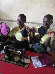 Ugandan young women holding up handmade sanitary towels from FIZZ mission trip