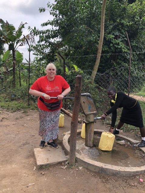 Girls' Brigade volunteer and Ugandan girl working at a water pump on FIZZ mission trip