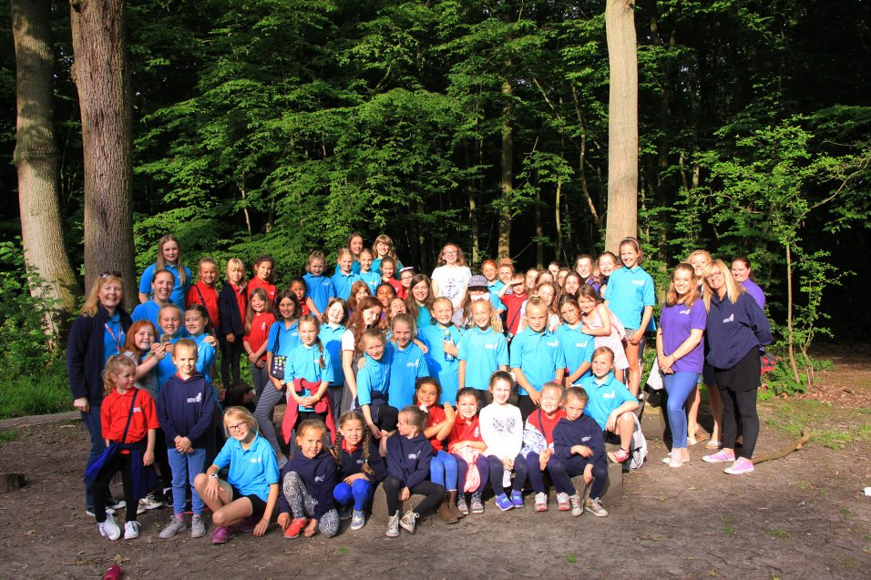 A large group of Girls' Brigade volunteers, girls and young people gathered in front of trees