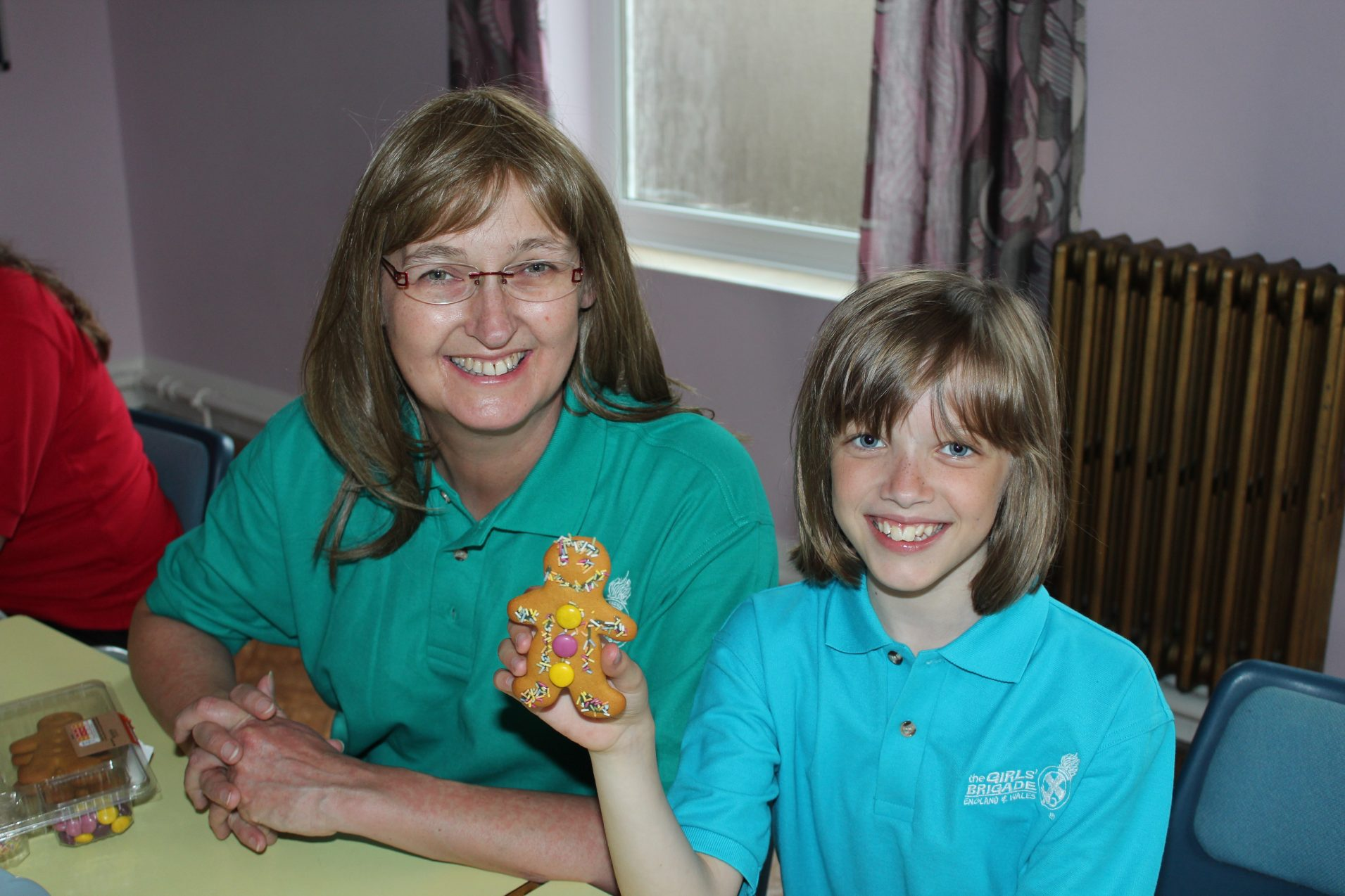 n:gage girls holding up decorated gingerbread man with Girls' Brigade volunteer