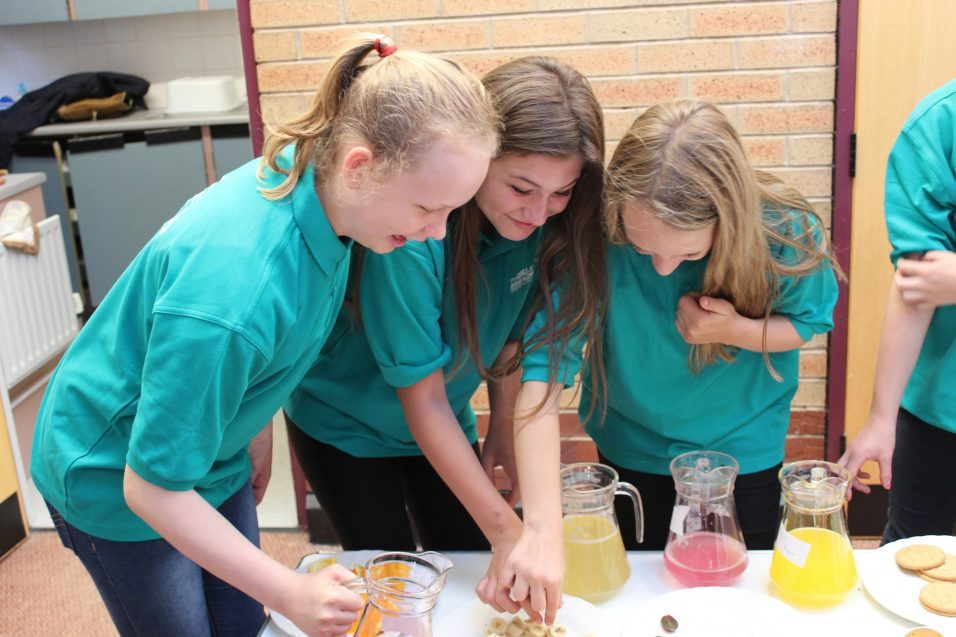 n:counta girls choosing biscuits and pouring juice at a table