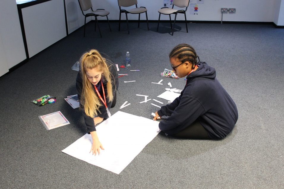 Girls' Brigade young leaders creating poster on floor