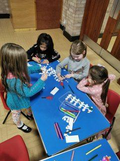 n:vestigate girls sat at table at Bromsgrove making paper chain people