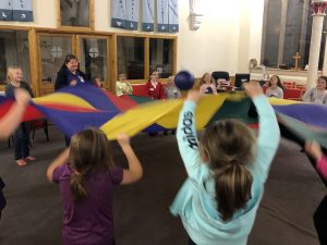 girls and volunteers playing with a parachute at 1st Ryton