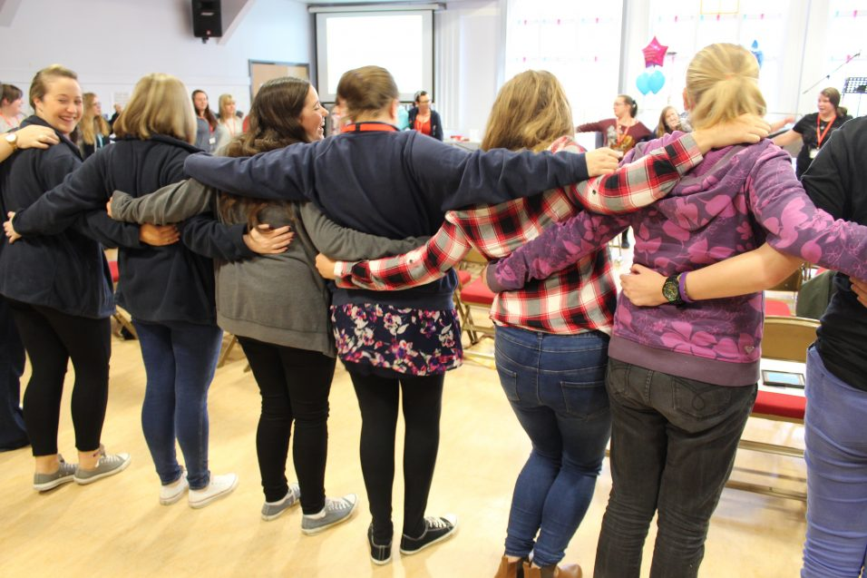 young women stood in a circle with arms around each other
