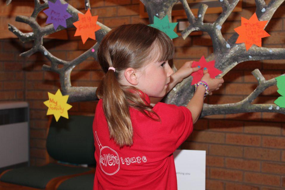 n:vestigate girl sticking star on prayer tree
