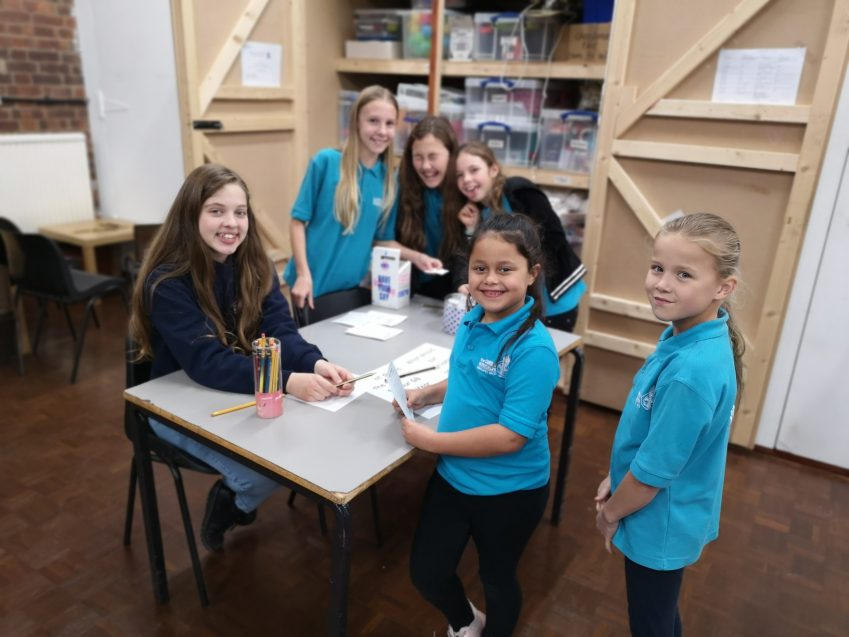 six n:gage girls laughing and smiling around table on UK parliament week