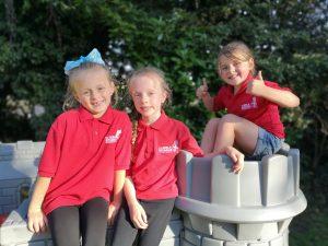 three n:vestigate girls sat on play castle smiling at camera