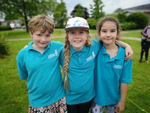 three n:gage girls with arm around each other at park