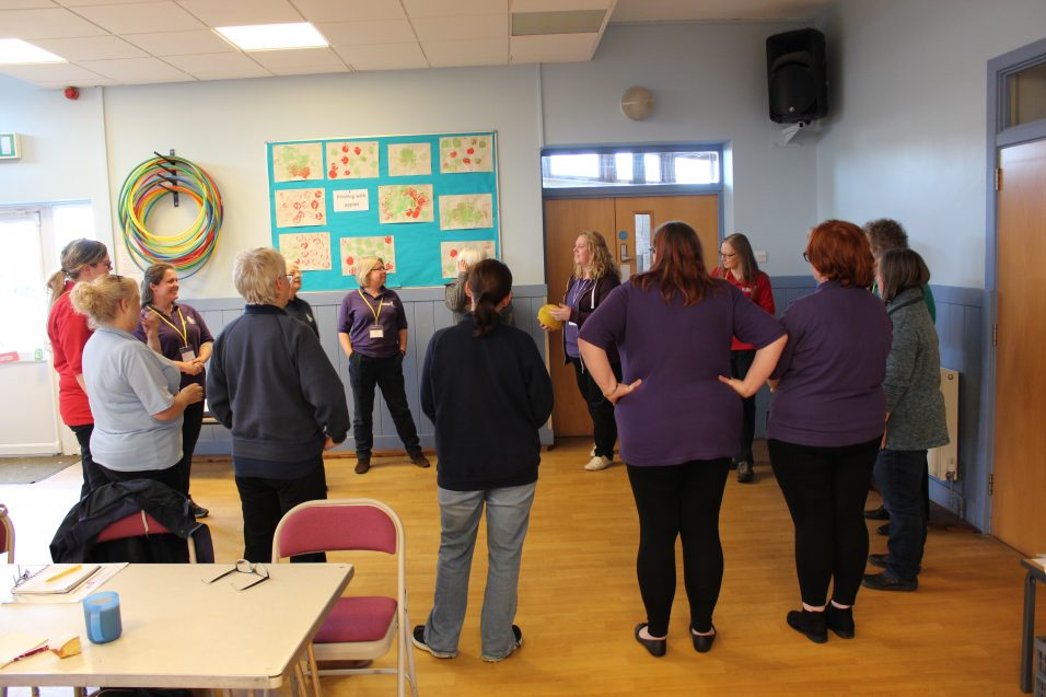 Girls' Brigade volunteers stood in circle with ball for training activity