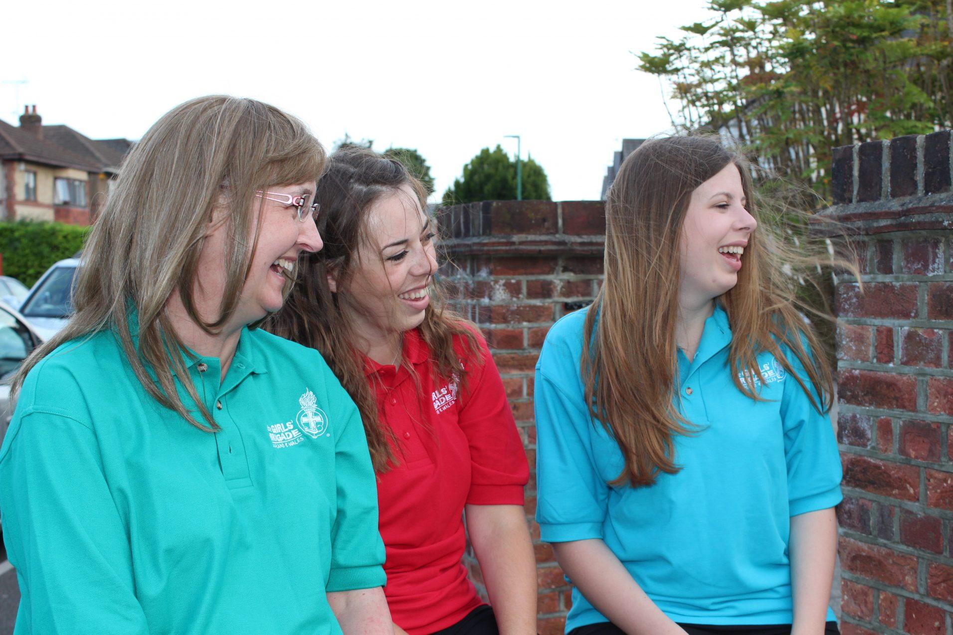 three Girls' Brigade volunteers sat on wall laughing