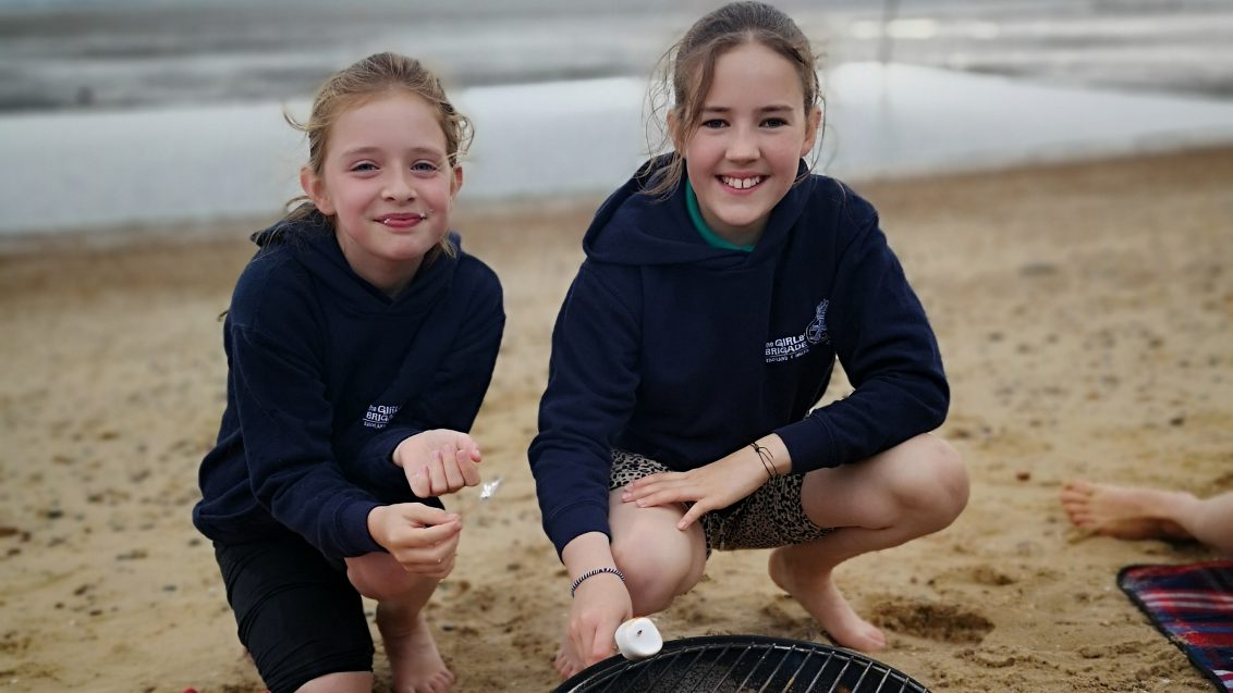 two girls toasting marshmallows on beach