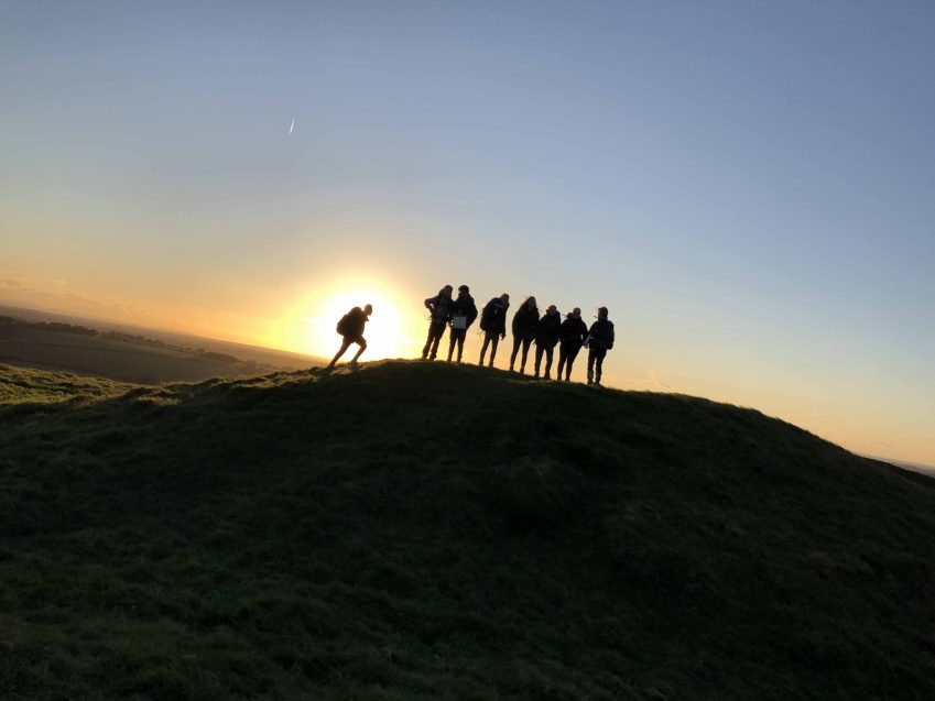 hikers in front of sunset