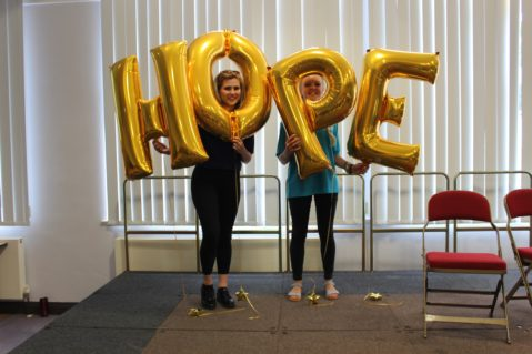 Two leaders holding HOPE balloons