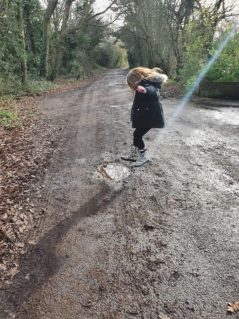 girl jumping into puddle