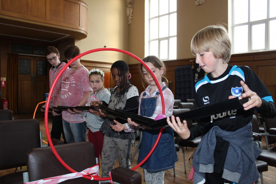 Six young people playing problem solving game
