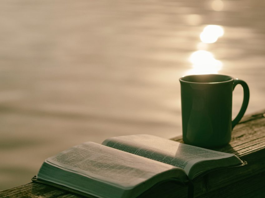 open Bible and coffee cup by the water